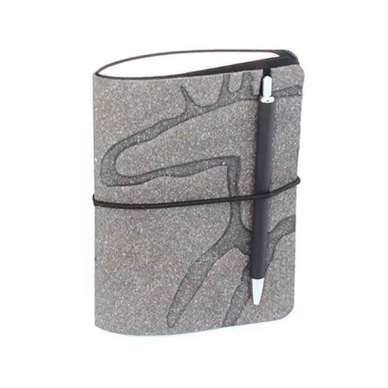 Harmaa uusionahkainen Pocket -vihko jossa preeglattuna Design Pylsyn Hirvi-kuvio.